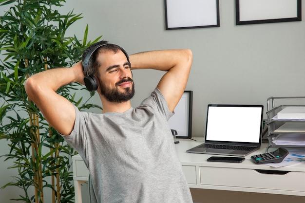 Mann, der kopfhörer benutzt, während er von zu hause aus arbeitet