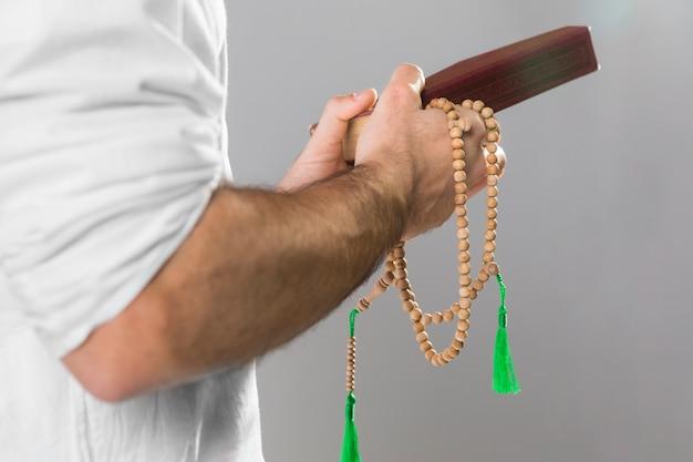 Mann, der koran und gebetsperlen hält