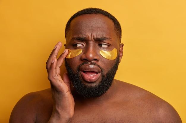 Mann, der kosmetische maske auf gesicht für dermatologie-hautpflege trägt