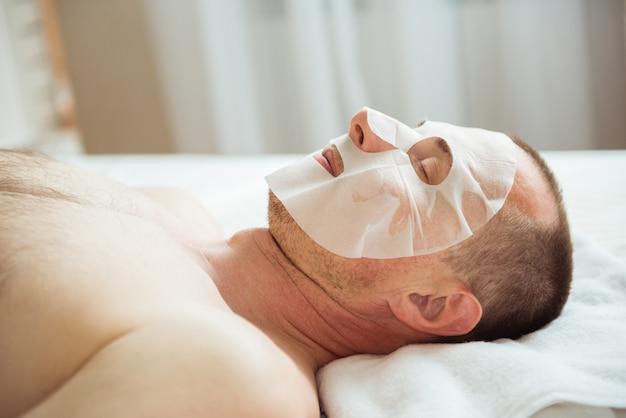 Mann, der kosmetische maske im spa-salon hat