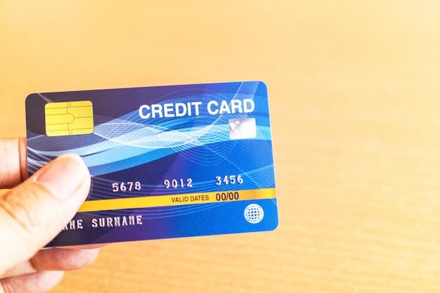 Mann, der kreditkarte auf laptop hält. online-shopping im internet mit einem laptop