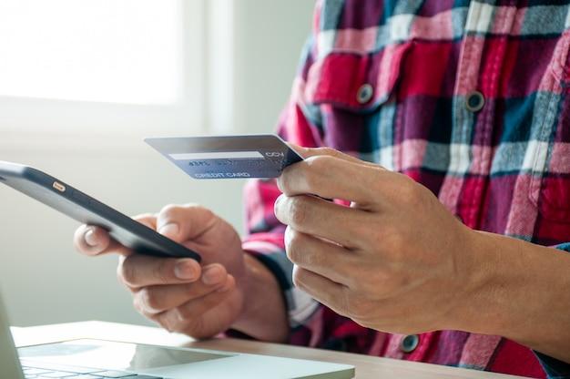 Mann, der kreditkarte für online-einkauf über smartphone verwendet