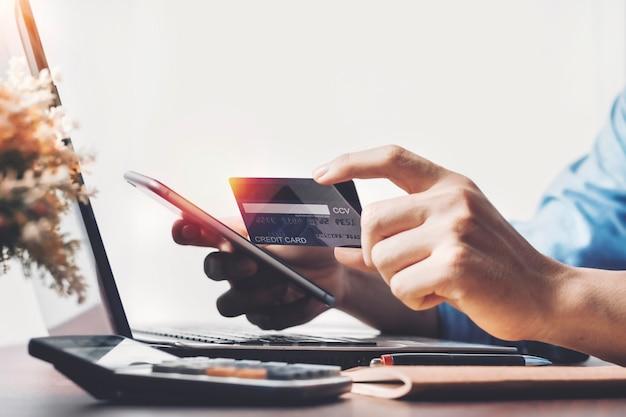 Mann, der kreditkarte hält, die online-zahlung nach dem online-kauf, internet-einkauf mit karte macht