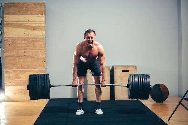 Mann, der kreuzhebenhantel über seinem kopf im modernen fitnesscenter tut.