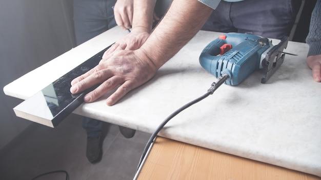 Mann, der küchenarbeitsplatte mit elektrischer säge schneidet.