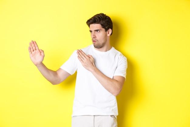 Mann, der kung-fu-fähigkeiten zeigt, kampfkunst-ninja-bewegung, im weißen t-shirt kampfbereit stehend, auf gelbem hintergrund stehend