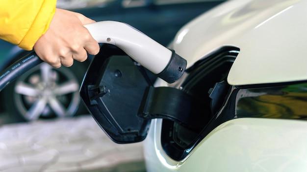 Mann, der ladegerät in ein weißes elektroauto einsteckt