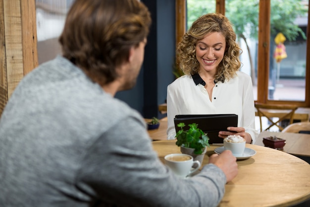 Mann, der lächelnde frau unter verwendung der digitalen tablette am kaffeehaus betrachtet