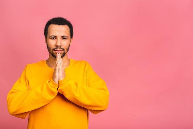 Mann, der lässig steht über isoliertem rosa betteln und beten mit händen zusammen mit hoffnungsausdruck