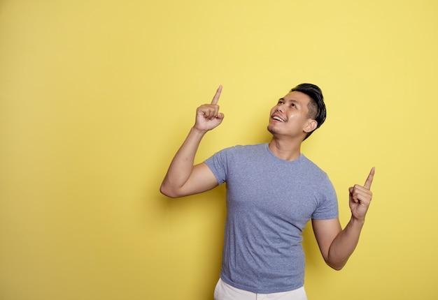 Mann, der lässigen t-shirt lächeln ausdruck zeigt leerzeichen zeigt. denkidee isoliert auf gelbem farbhintergrund