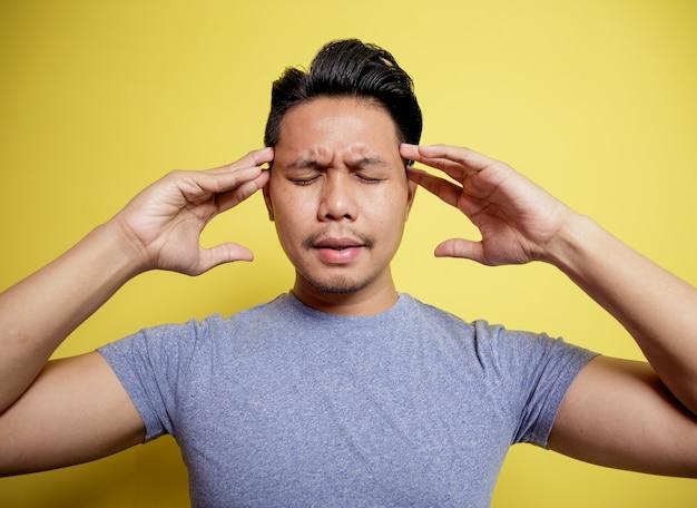 Mann, der lässigen t-shirt schwindelerregenden ausdruck hält, der kopf lokalisiert auf einem gelben farbhintergrund hält