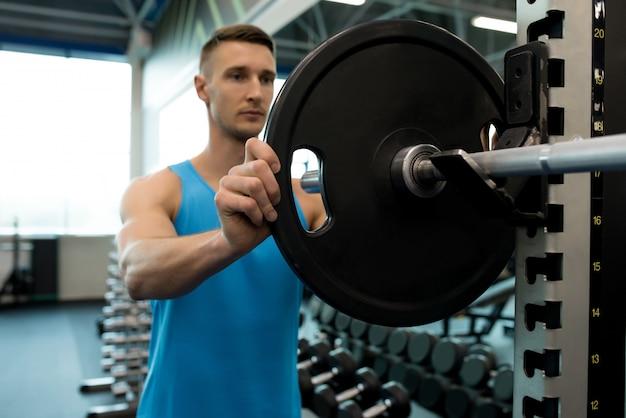Mann, der langhantel im fitnessstudio zusammenbaut