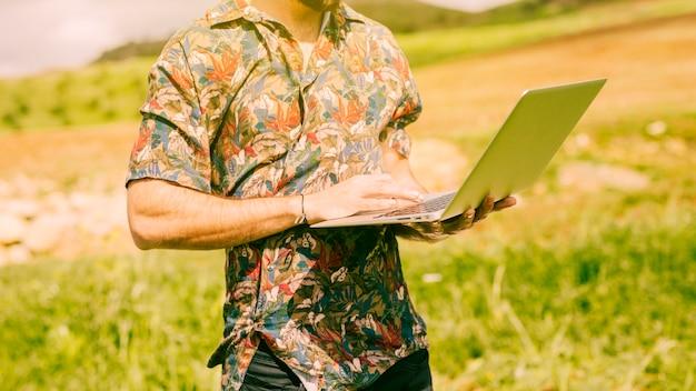 Mann, der laptop auf dem gebiet hält
