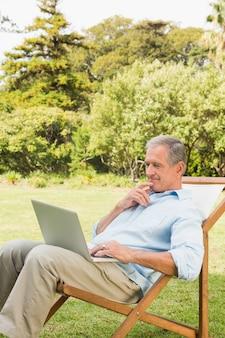 Mann, der laptop auf sonnenruhesessel verwendet