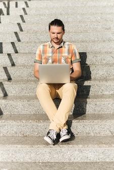 Mann, der laptop auf treppen verwendet