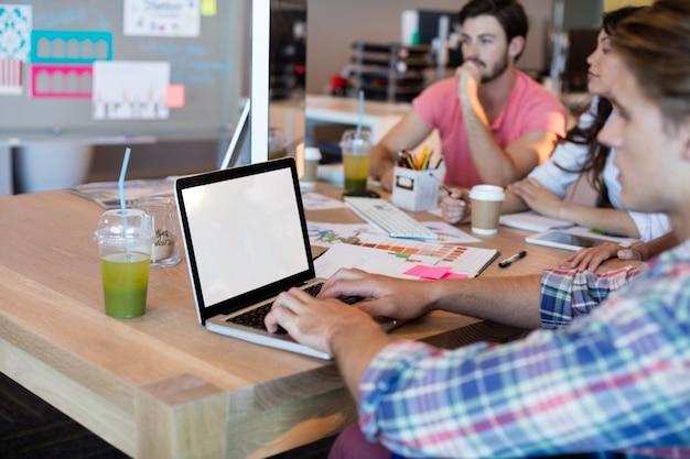 Mann, der laptop benutzt, während er mit seinem team im büro arbeitet