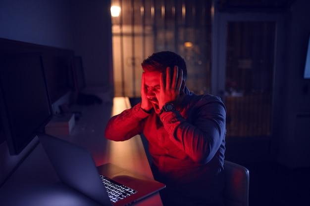 Mann, der laptop betrachtet und spät in der nacht im büro sitzt.