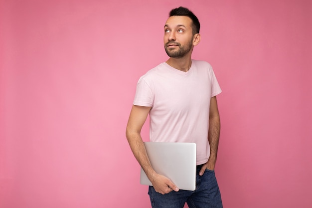 Mann, der laptop-computer hält, der im t-shirt auf lokalisiertem rosa nach oben schaut