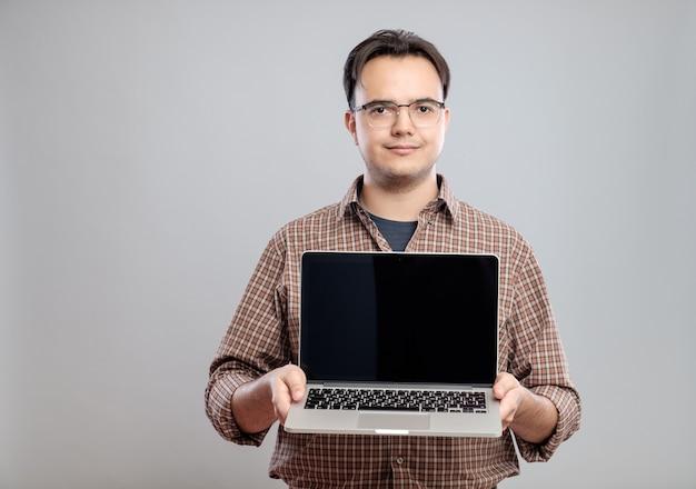 Mann, der laptop-computer hält und zeigt