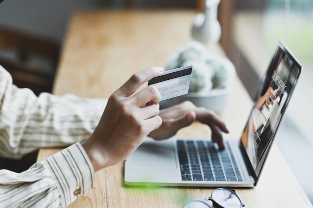Mann, der laptop-computer verwendet und kreditkarte für online-banking hält.