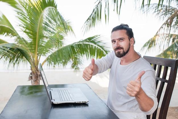 Mann, der laptop-computer verwendet, während am strandcafé nahe palmen sitzt und daumen oben zeigt