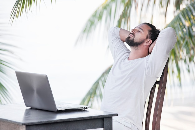 Mann, der laptop-computer verwendet, während an strandcafébar nahe palmen sitzt