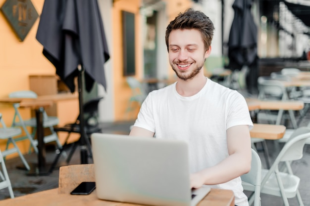 Mann, der laptop für fernarbeit im café verwendet