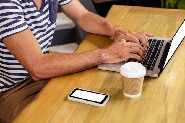 Mann, der laptop in der cafeteria verwendet
