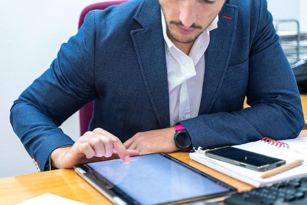 Mann, der laptop in seinem büro beim arbeiten über versicherung und bankwesen betrachtet