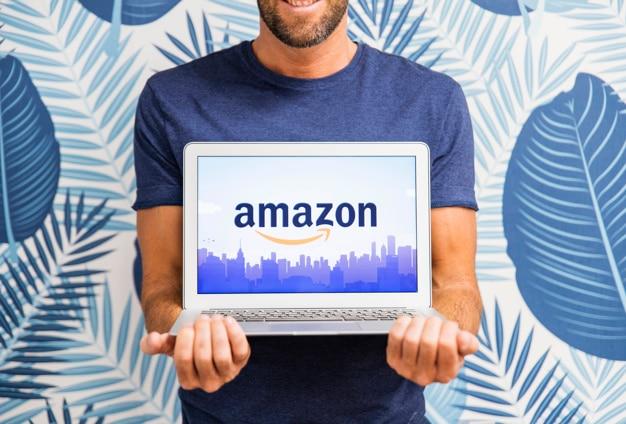 Mann, der laptop mit amazonas-site hält