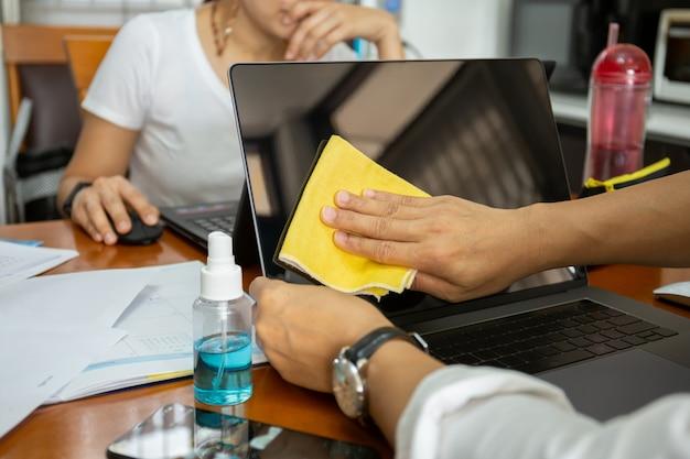Mann, der laptop mit gelbem mikrofasertuch mit flüssigem alkoholdesinfektionsmittel reinigt.