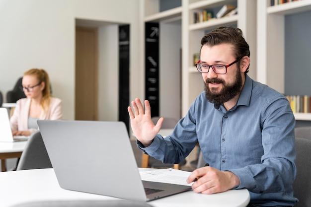 Mann, der laptop mittlerer schuss winkt