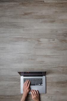Mann, der laptop-tastatur auf rustikalem verwittertem hölzernen schreibtischoberflächenhintergrund mit kopienraum verwendet