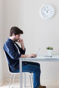 Mann, der laptop und das denken verwendet