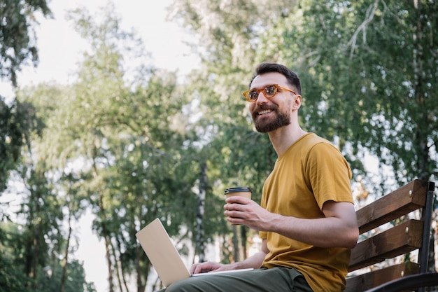 Mann, der laptop verwendet, tasse kaffee hält und im park arbeitet, der auf bank sitzt