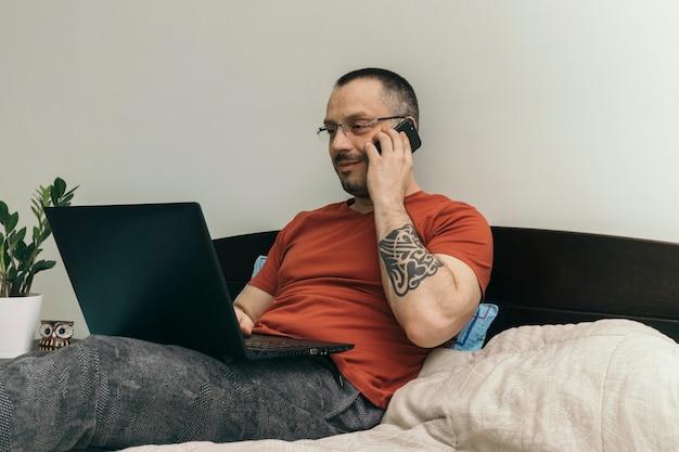 Mann, der laptop verwendet und am telefon auf bett spricht