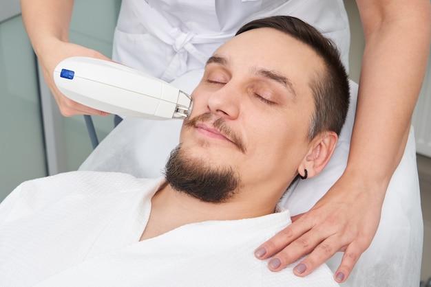 Mann, der laserbehandlung an der schönheitsklinik hat