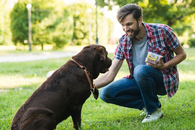 Mann, der lebensmittel im behälter spielt mit hund hält
