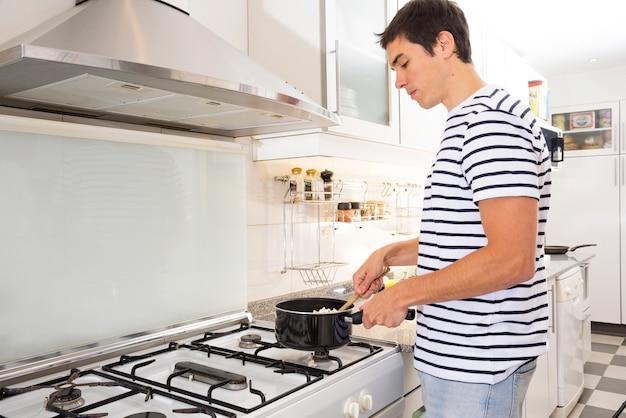 Mann, der lebensmittel in der küche kocht