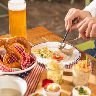Mann, der leckere deutsche wurst, bier schneidet