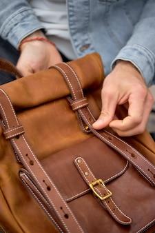 Mann, der ledernen braunen handgemachten rucksack auf spaziergang nimmt, nahaufnahmefoto.