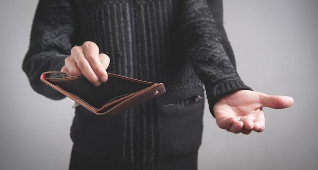 Mann, der leere brieftasche hält. kein geld