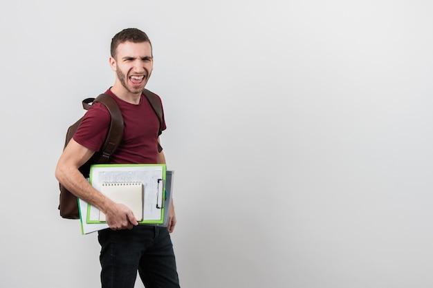 Mann, der lustige gesichter mit exemplarplatzhintergrund bildet