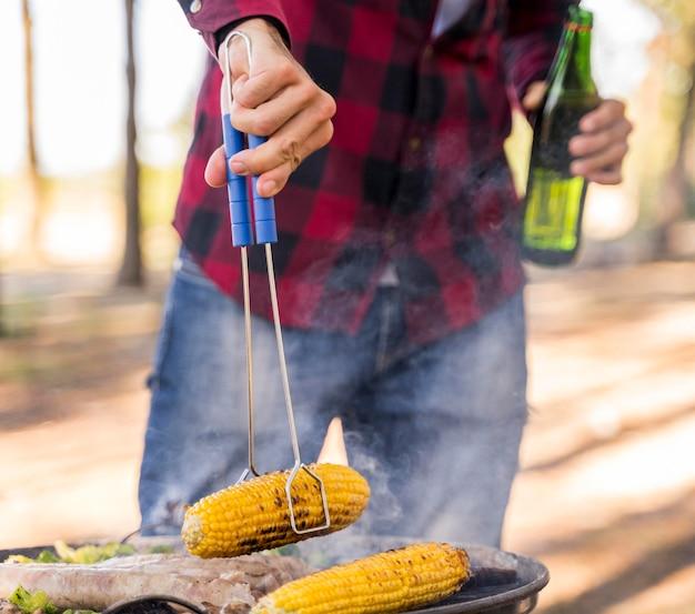 Mann, der mais auf grill während des trinkens des bieres röstet