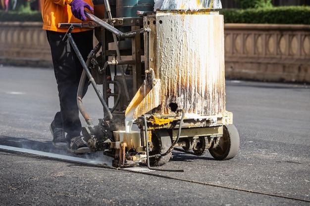 Mann, der maschine verwendet, um verkehrslinie streifen auf der straße zu machen