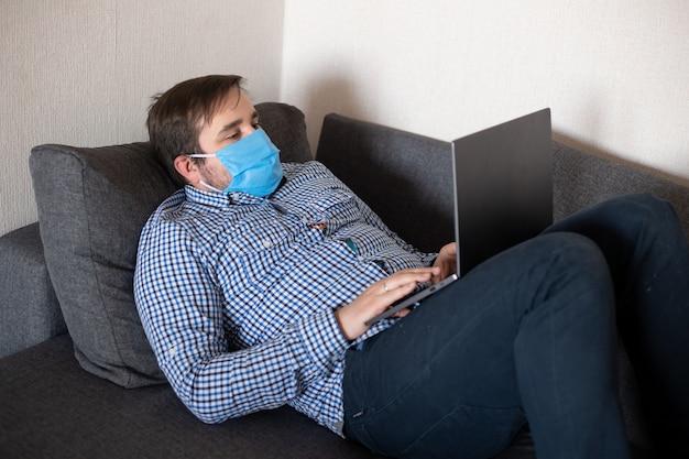 Mann, der maske arbeitet, die mit computer vom hauptbüro arbeitet, das auf sofa, coronavirus, krankheit, infektion, quarantäne, medizinische maske liegt
