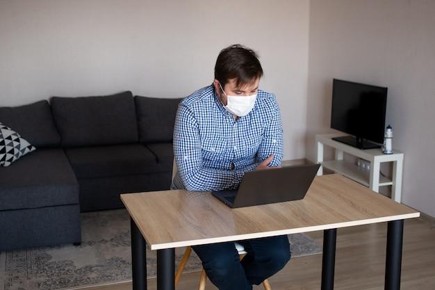 Mann, der maske arbeitet, die mit laptop vom hauptbüro, coronavirus, krankheit, infektion, quarantäne, medizinische maske arbeitet