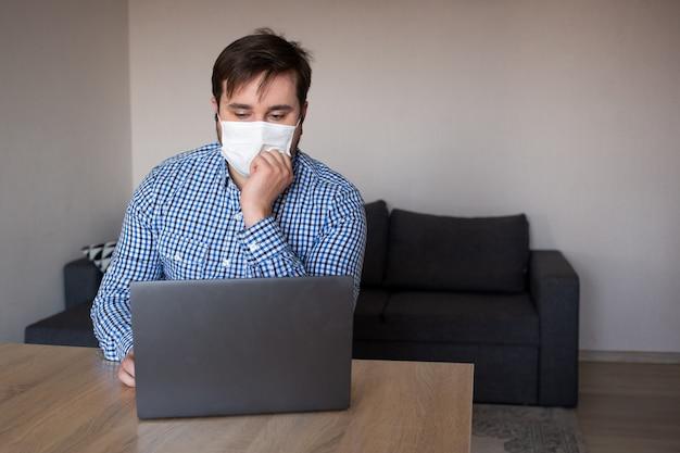 Mann, der maske trägt, die an seinem laptop von zu hause, coronavirus, krankheit, infektion, quarantäne, medizinische maske arbeitet