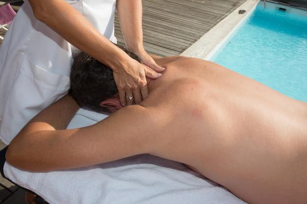 Mann, der massage durch einen pool getan hat