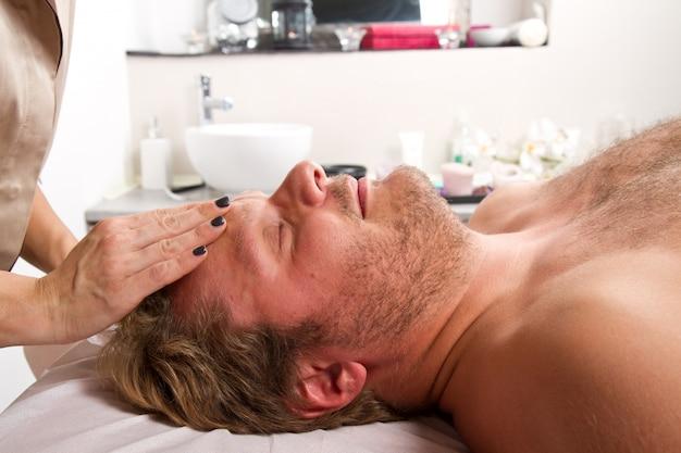 Mann, der massage in der schönheitsmitte erhält